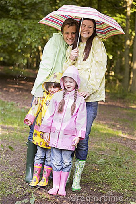 Family Outdoors In Rain With Umbrella Smiling Royalty Free